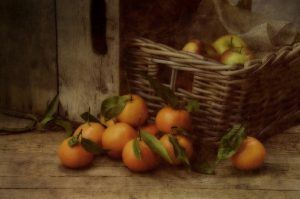 Clementines on wood and Apples in a basket