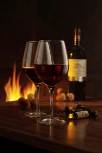 2 red wine glasses with bottle and fire in the background to illustrate Drinks Photography