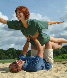 Girl supported by man on his back - she's flying