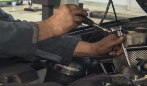 Hands of a mechanic working on car
