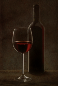 Red wine glass with bottle in the background